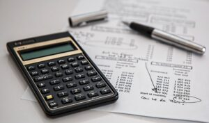Accounting documents next to a calculator and pen